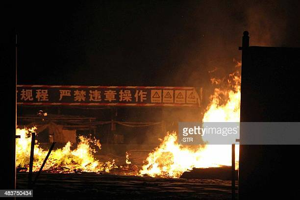 Flames rise as a banner in the background reads 'no illegal operations' at the site of a series of explosions in Tianjin early on August 13 2015 A...