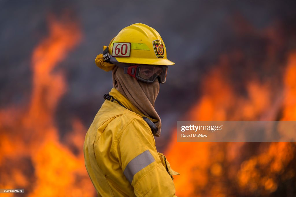 Flames rise behind a firefighter at the La Tuna Fire on September 2, 2017 near Burbank, California. Los Angeles Mayor Eric Garcetti said at a news conference that officials believe the fire, which is at 5,000 acres and growing, is the largest fire ever in L.A. People have been evacuated from hundreds of homes in Sun Valley, Burbank and Glendale. About 100 Los Angles firefighters are expected to return soon from Texas, where they've been helping survivors from Hurricane Harvey.
