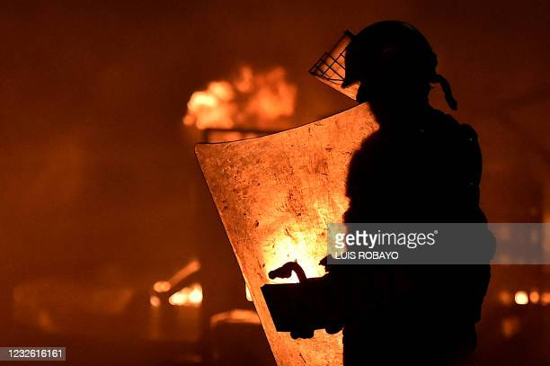 Flames rise from a burning barricade behind a riot police officer during clashes following a protest against a tax reform bill launched by President...