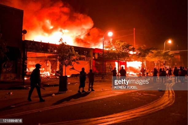 TOPSHOT Flames rise from a liquor store and shops near the Third Police Precinct on May 28 2020 in Minneapolis Minnesota during a protest over the...