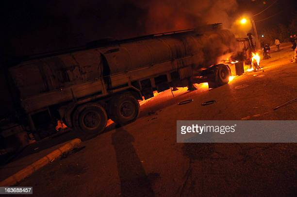 Flames rise from a petrol tanker after it was set on fire by protesters in the northern Lebanese city of Tripoli on March 14 to halt it from reaching...