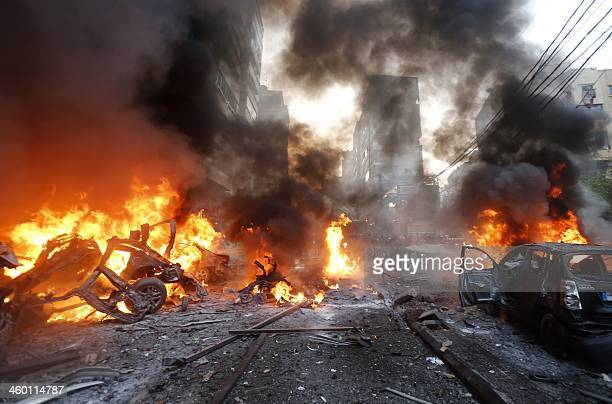 Flames rise from burning cars at the site of a car bomb that targeted Beirut's southern suburb of Haret Hreik on January 2 2014 A large car bomb...