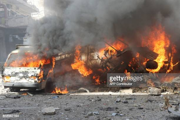 Flames rise from the wreckage of vehicles following a reported air strike on a vegetable market in Maaret alNuman in Syria's northern province of...