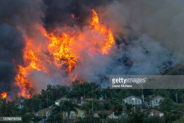 Flames rise near homes during the Blue Ridge Fire on October 27, 2020 in Chino Hills, California. Strong Santa Ana Winds gusting to more than 90...