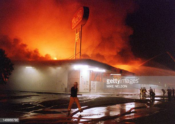 Flames roar from a Thrifty Drug store in the Crenshaw area of Los Angeles 29 April 1992 Riots broke out in Los Angeles 29 April 1992 after a jury...