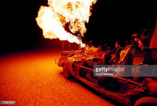 Flames shoot from an art car as it drives across the desert during the15th annual Burning Man festival September 2 2000 in the Black Rock Desert near...