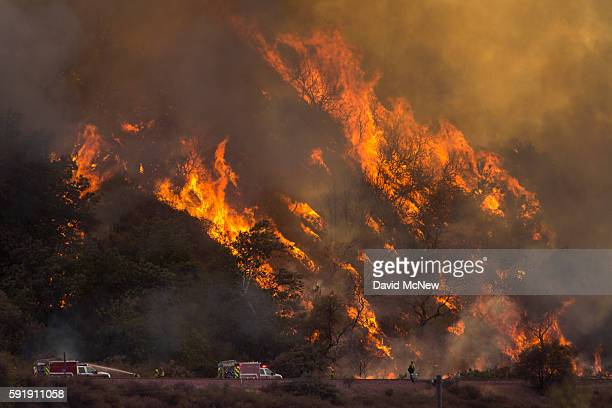 Flames spread up a hillside near firefighters at the Blue Cut Fire on August 18 2016 near Wrightwood California An unknown number of homes and...