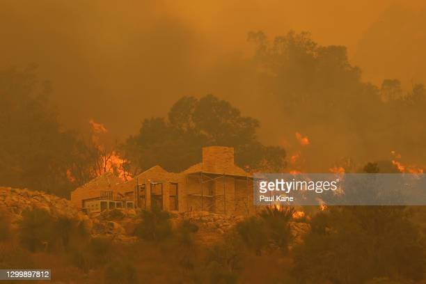 Flames surround a property under construction off Copley Road in Upper Swan on February 02, 2021 in Perth, Australia. Up to 30 homes are feared lost...