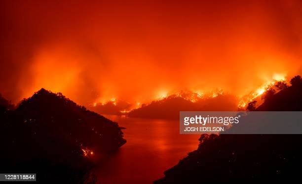 Flames surround Lake Berryessa during the LNU Lightning Complex fire in Napa, California on August 19, 2020. - Thousands of people fled their homes...