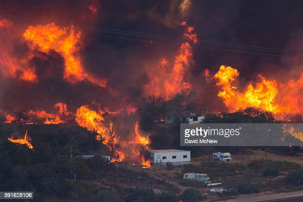 Flames sweep through a rural community at the Blue Cut Fire on August 17 2016 near Wrightwood California An unknown number of homes and businesses...