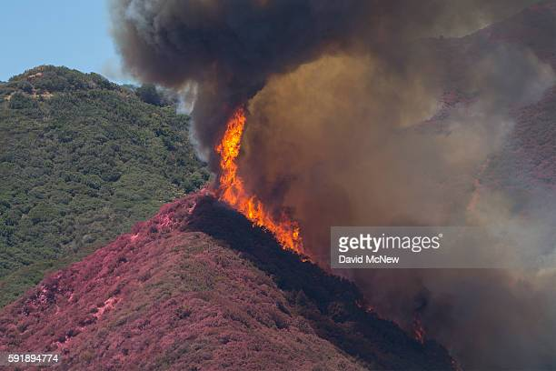 Flames threaten to jump a ridge that firefighting aircraft have painted red with fire retardant above Cajon Boulevard at the Blue Cut Fire on August...