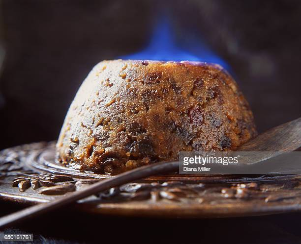 Flaming brandy Christmas pudding on wooden board