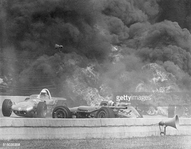 Flaming Fire Indianapolis Indiana Racing driver Johnny Boyd skids past Ronnie Duman in his burning auto as the auto of Eddie Sachs goes up in flames...