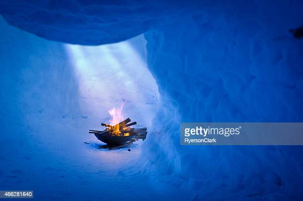 Flaming Fire pit in a Snow Cave with Sunlight Beams.