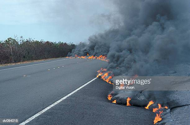flaming lava flow moving across a road - lava stock pictures, royalty-free photos & images