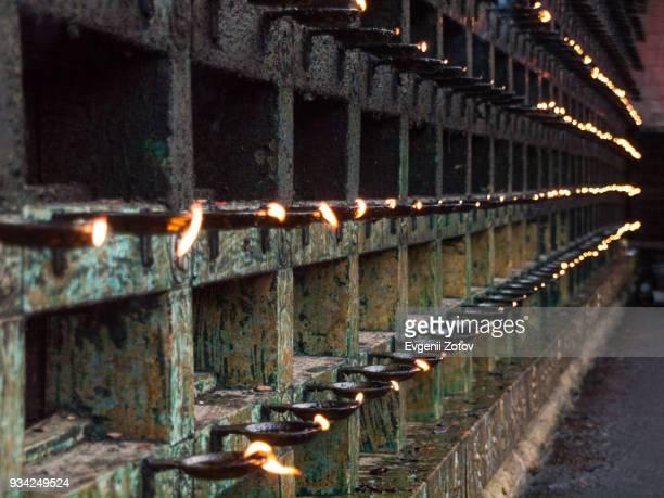 Flaming oil lamps on the wall surrounding Mahadeva Temple in Ettumanoor, Kerala, India