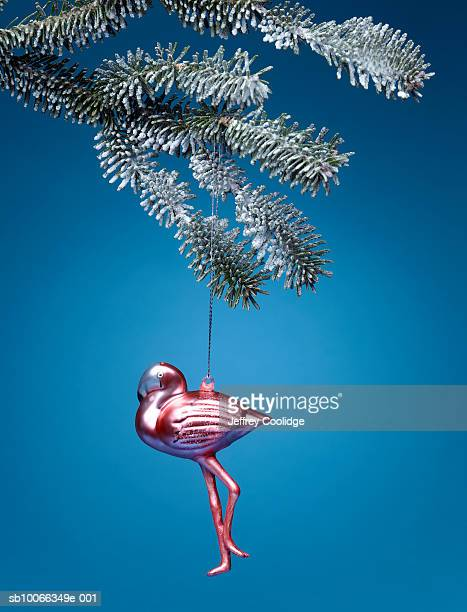 Flamingo Christmas ornament hanging from firtree branch