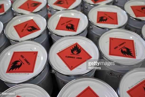 Flammable liquid hazard signs sit on tins of Grey Aviox finish paint inside the Akzo Nobel NV paint and coatings factory in Sassenheim Netherlands on...
