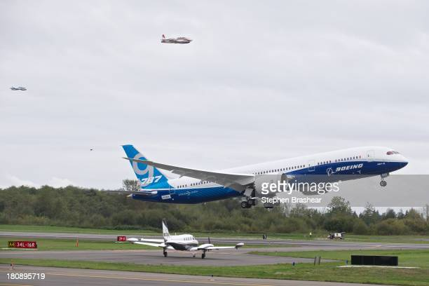 Flanked by a pair of chase planes a Boeing 7879 Dreamliner lifts off for its first flight September 17 2013 at Paine Field in Everett Washington The...