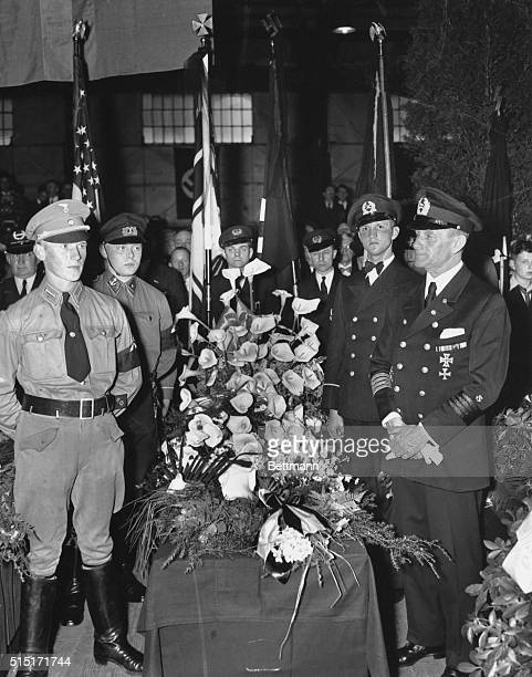 Flanked by an honor guard of uniformed Nazi party members and personnel from the Hamburg-America line , the casket bearing the remains of Captain...