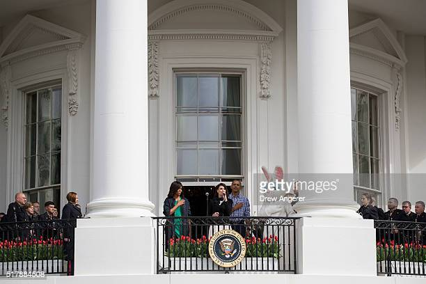 Flanked by first lady Michelle Obama and President Barack Obama Idina Menzel sings the National Anthem during the annual White House Easter Egg Roll...