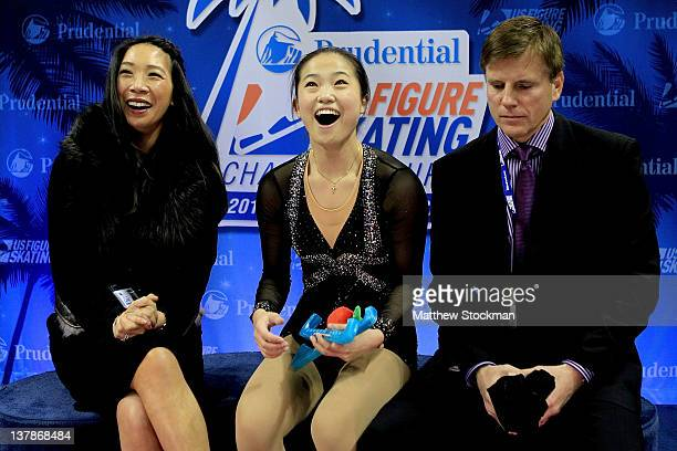 Flanked by her coaches Karen Kwan Oppegard and Peter Oppegard Caroline Zhang celebrates in the Kiss and Cry after the Ladies Free Skate during the...