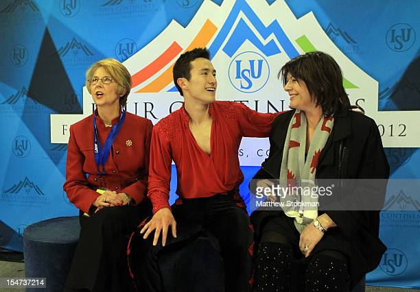 Flanked by his coaches Christy Krall and Kathy Johnson Patrick Chan of Canada watches his scores in the Kiss Cry after the Men's Free Skate during...