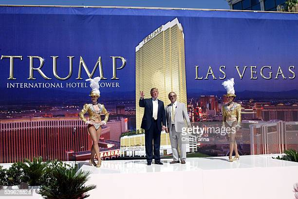Flanked by Las Vegas showgirls Real estate mogul Donald Trump and New Frontier hotel owner Phil Ruffin pose during a groundbreaking ceremony for...