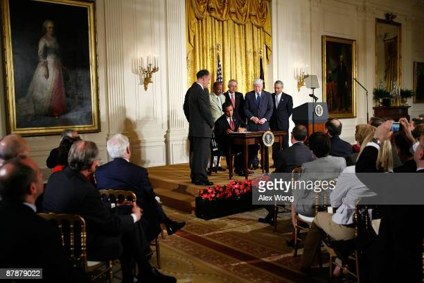 Flanked by lawmakers US President Barack Obama signs the Fraud Enforcement and Recovery Act into law as Rep John Larson Senate Democratic Leader Sen...