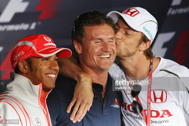 Flanked by Lewis Hamilton of Great Britain and McLaren Mercedes , David Coulthard of Great Britain and Red Bull Racing is kissed by Jenson Button of...