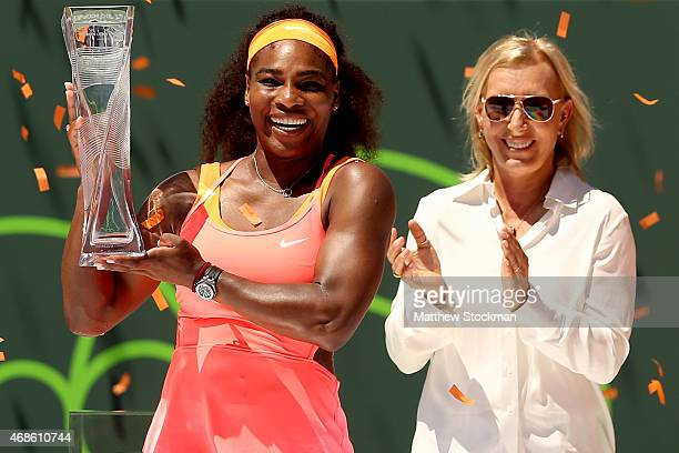 Flanked by Martina Navratilova Serena Williams poses with the Butch Buchholz Trophy after defeating Carla Suarez Navarro of Spain during the final on...