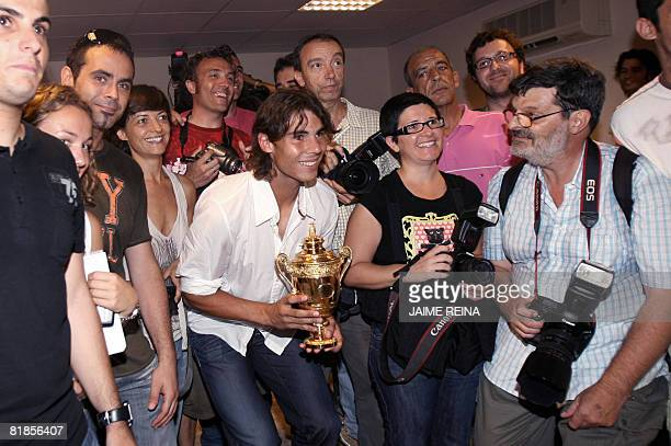 Flanked by media members, Spain's Rafael Nadal poses with his Wimbledon trophy at the Manacor's town hall, Mallorca, Balearics Islands on July 08,...