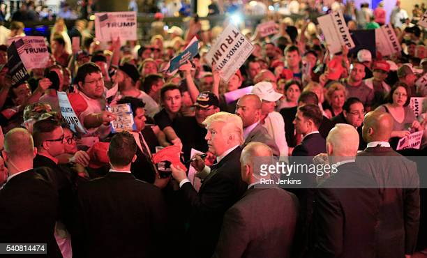 Flanked by members of the Secret Service Republican presidential candidate Donald Trump center signs for supporters as stage lights paint the dance...