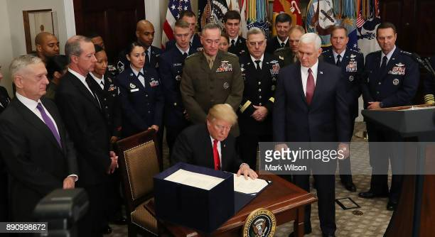 Flanked by members of the US military US President Donald Trump signs the HR 2810 National Defense Authorization Act for fiscal year 2018 in the...