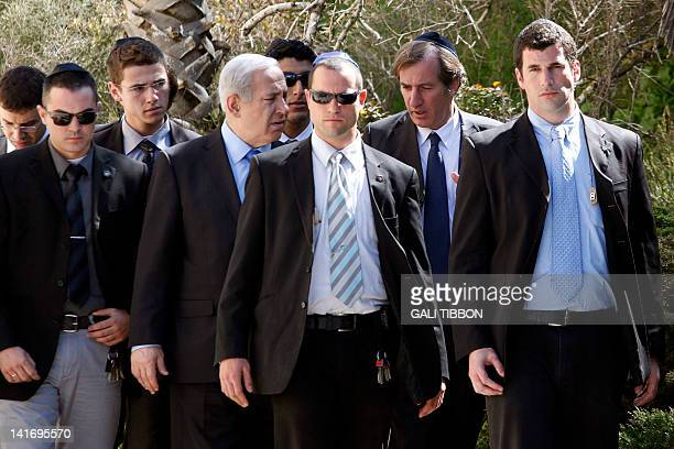 Flanked by security guards Israeli Prime Minister Benjamin Netanyahu and French ambassador to Israel Christophe Bigot leave after offering their...