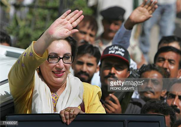 Flanked by security personnel carrying automatic weapons former Pakistani premier Benazir Bhutto waves as she boards her car in Karachi 21 October...