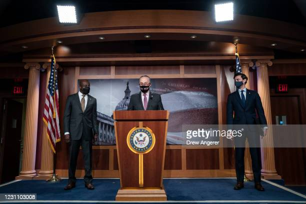 Flanked by Sen. Raphael Warnock and Sen. Jon Ossoff , Senate Majority Leader Chuck Schumer speaks during a news conference at the U.S. Capitol on...