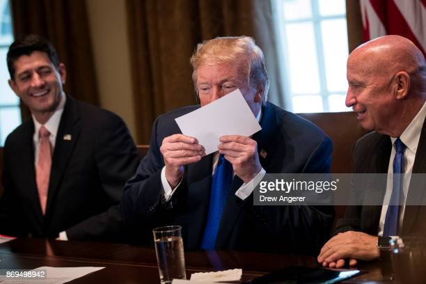 Flanked by Speaker of the House Paul Ryan and House Ways and Means Committee chairman Rep Kevin Brady President Donald Trump kisses an example of...