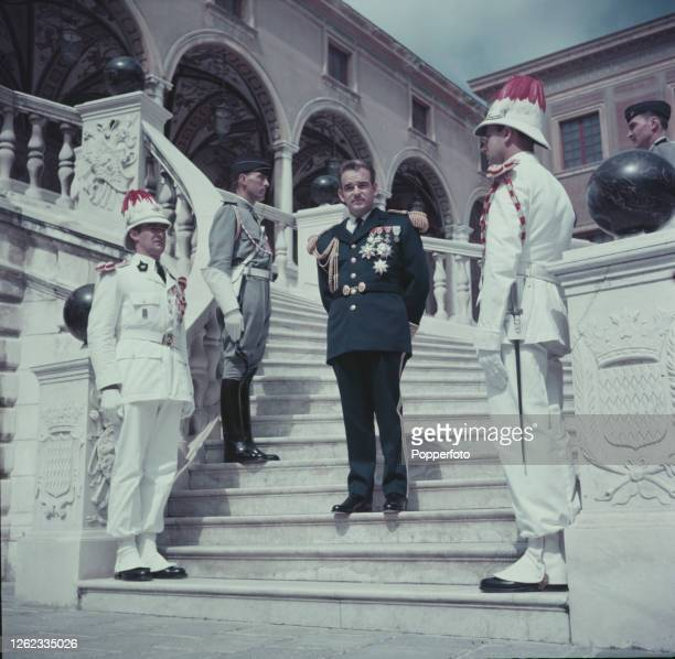Flanked by three members of the palace guard, Rainier III, Prince of Monaco stands on steps dressed for a state occasion, at a Palace residence in...
