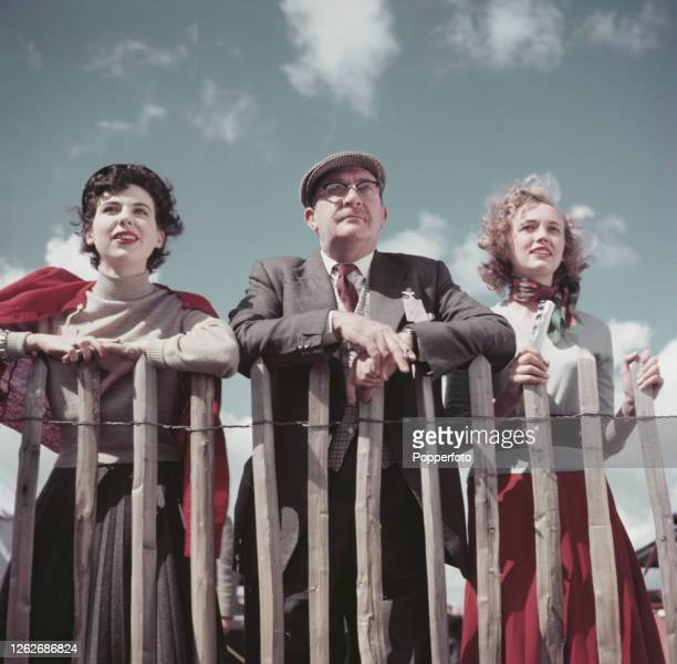 Flanked by two female racegoers English journalist and television presenter Gilbert Harding attends a race meeting at Goodwood Racecourse near...