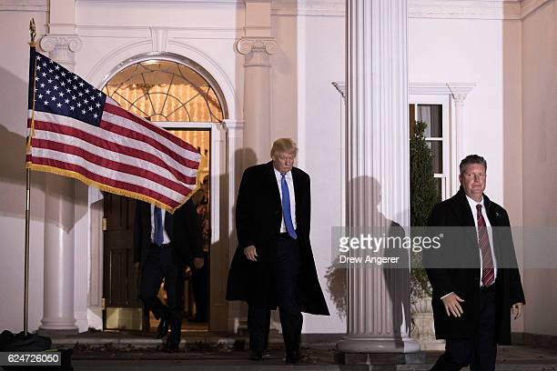 Flanked by US Secret Service agents Presidentelect Donald Trump leaves the clubhouse following a full day of meetings at Trump International Golf...