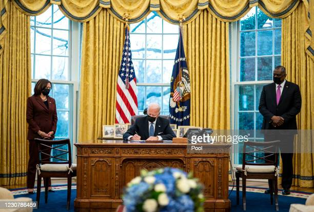 Flanked by Vice President Kamala Harris and Secretary of Defense Lloyd Austin , U.S. President Joe Biden signs an executive order in the Oval Office...