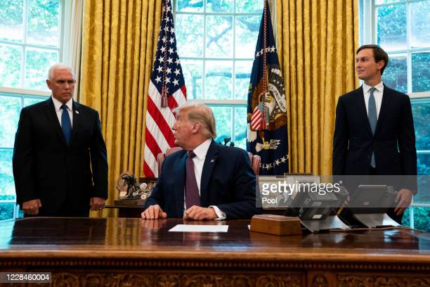 Flanked by Vice President Mike Pence and advisor Jared Kushner , U.S. President Donald Trump speaks in the Oval Office to announce that Bahrain will...