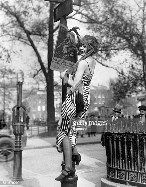 A flapper hangs a poster to advertise the Greenwich Village Halloween Ball at which Paul Whiteman is to perform
