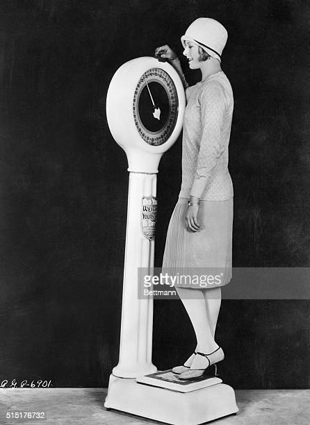 Flapper weighing herself on scale Photograph ca 1920