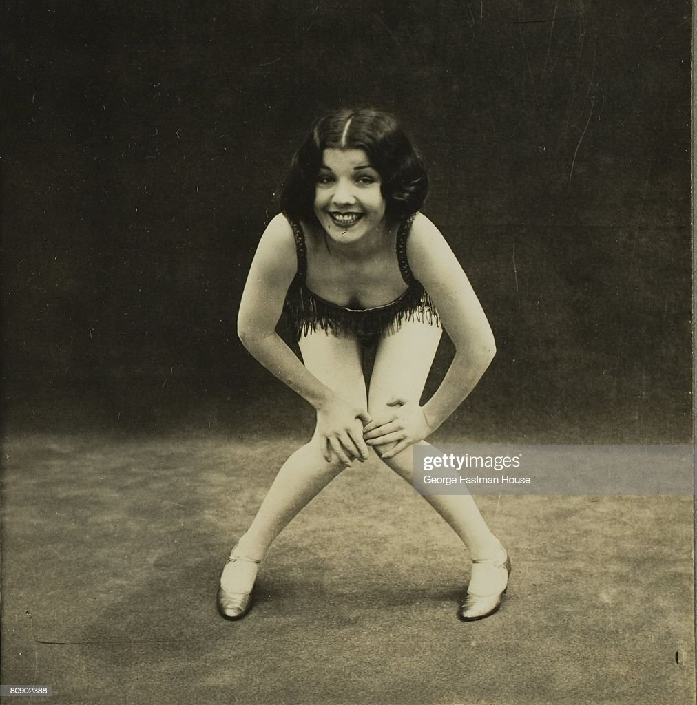 A flapper, with arms akimbo and hands on knees, smiles as she demonstrates some of the dance moves of the 1920s,