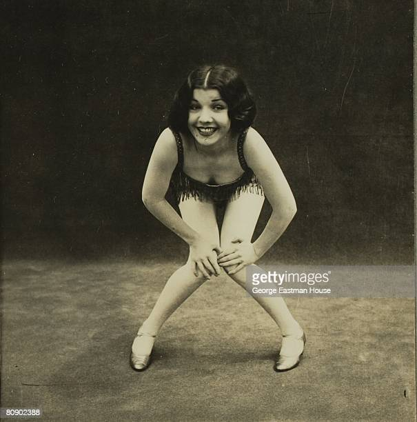 A flapper with arms akimbo and hands on knees smiles as she demonstrates some of the dance moves of the 1920s