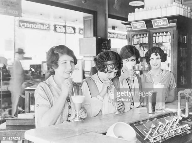 Flappers at a soda fountain drinking milk shakes in 1926