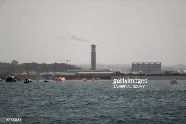 Flare is lit as French fishing boats protest in front of the port of Saint Helier off the British island of Jersey to draw attention to what they see...