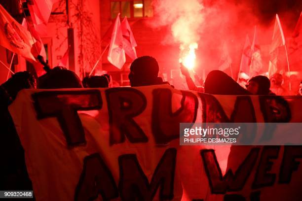 A flare is lit as people protest against the attendance of the US president to the upcoming Davos World Economic Forum on January 23 in central...